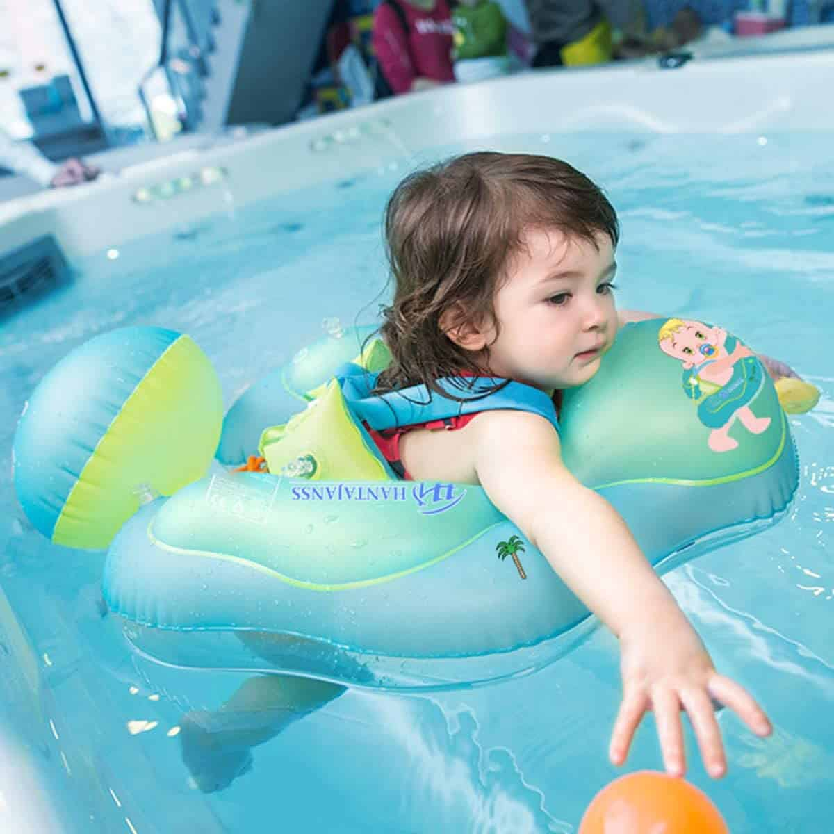 This is an image of a baby girl playing on a baby pool swim float. She is having fun while trying to swim and reach to toys on the pool float.